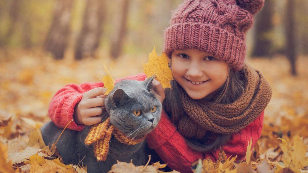 Enfant avec un chat noir dans la forêt. Nous pouvons voir qu'avoir la responsabilité d'un animal pour un enfant est signe de développement personnel.